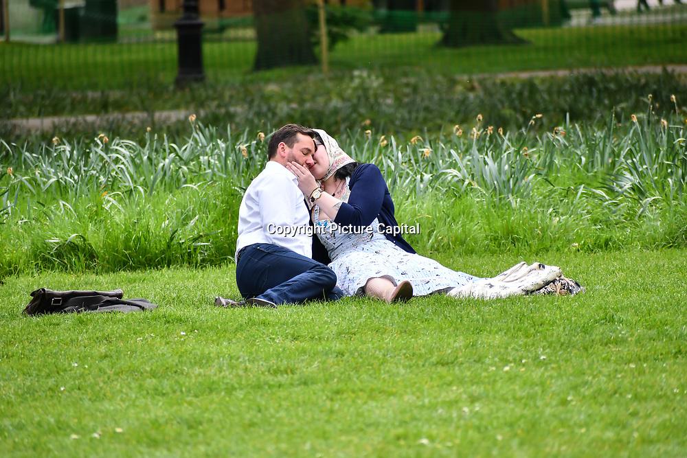 A romantic couple kissing at Green park on 23 April 2019, London, UK.