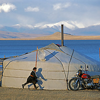 MONGOLI, Darhad Valley. Nomad girl plays hide and seek around ger next to (Lake) Dood Nuur.The motorcycle is a sign of family wealth.