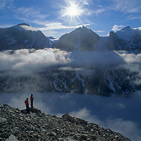 BAFFIN ISLAND, Canada, Climbers on huge ledge, Great Sail Peak, above frozen lake in Stewart Valley.