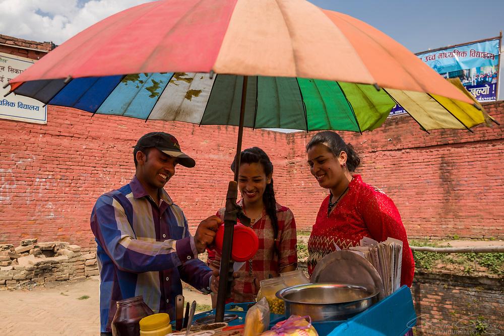 A street vendor preparing snacks for customers beneath a colourful, rainbow umbrella, Durbar Square, Bhaktapur, Nepal