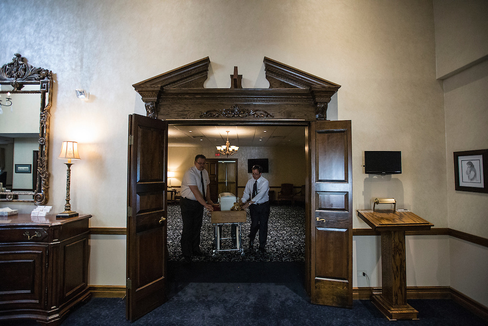 """Glueckert Funeral Home Funeral Directors John Glueckert (L) and David Blessman move the casket containing the remains of an abandoned newborn baby from the chapel in Arlington Heights, Illinois, United States, June 19, 2015. More than a year after the boy was found dead in a plastic shopping bag on a Chicago sidewalk, Glueckert and a non-profit group """"Rest in His Arms"""" stepped in to provide funeral and burial services. REUTERS/Jim Young"""