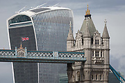 The British Union Jack flag flies from the high-level walkway of Victorian-era Tower Bridge, near the modern Walkie Talkie building aka 20 Fenchurch Street, on 14th September 2017, in London, England.