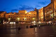 A couple shares a kiss in Piazza del Campo, the center of Siena, Tuscany, Italy.