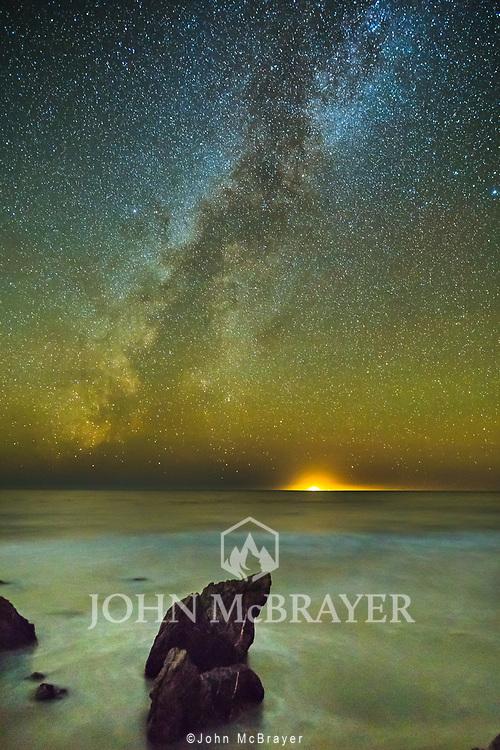 A fishing boat beams like a small sun on the horizon.  Taken on the Pacific Coast near Big Sur. © John McBrayer