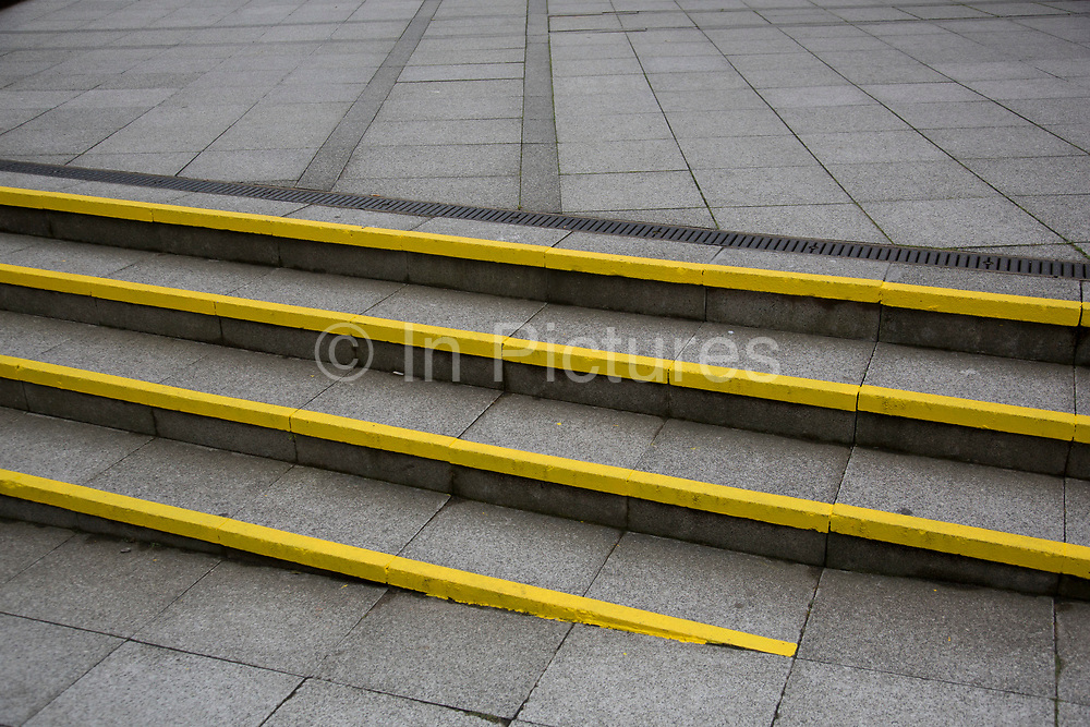 Yellow warning strips painted onto some steps creating a stripes pattern in London, England, United Kingdom.