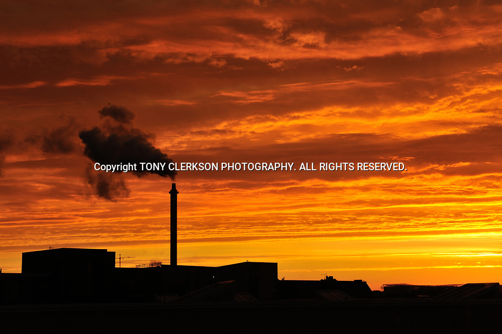 Sunrise over the east end of Glasgow with the chimey of Strathclyde distillery and Celtic Park silhoutted against the red sky