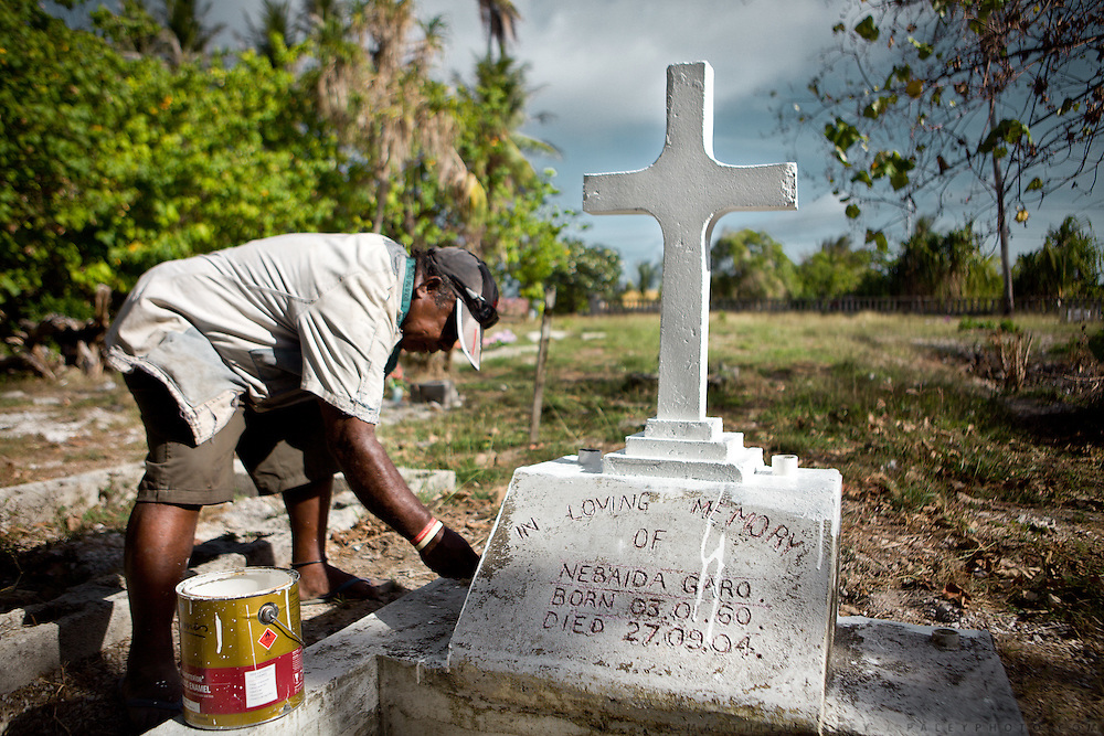 Shortly before Christmas, Jeffrey Garo is painting new the tumb of his wife, Nebaida Garo, who died of Diabetes at the age of 44. At a cemetery in Aiwo district...Nauru has the world's highest level of type 2 diabetes, with more than 40% of the population affected. Life expectancy on Nauru in 2006 was 58 years for males and 65 years for females..Nauru is the world's fattest country, with 94% of its population being overweight. One of the main reason is eating habits of Nauruans. .They rarely cook. Traditional food includes fish and coconut. But these days they especially enjoy Spam and Corned Beef and eat a lot of rice. Nauruans do not grow any vegetables...Nauru, officially the Republic of Nauru is an island nation in Micronesia in the South Pacific.  Nauru was declared independent in 1968 and it is the world's smallest independent republic, covering just 21square kilometers..Nauru is a phosphate rock island and its economy depends almost entirely on the phosphate deposits that originate from the droppings of sea birds. Following its exploitation it briefly boasted the highest per-capita income enjoyed by any sovereign state in the world during the late 1960s and early 1970s..In the 1990s, when the phosphate reserves were partly exhausted the government resorted to unusual measures. Nauru briefly became a tax haven and illegal money laundering centre. From 2001 to 2008, it accepted aid from the Australian government in exchange for housing a Nauru detention centre, with refugees from various countries including Afghanistan and Iraq..Most necessities are imported on the island..Nauru has parliamentary system of government. It had 17 changes of administration between 1989 and 2003. In December 2007, former weight lifting medallist Marcus Stephen became the President.