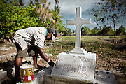 Shortly before Christmas, Jeffrey Garo is painting new the tumb of his wife, Nebaida Garo, who died of Diabetes at the age of 44. At a cemetery in Aiwo district...Nauru has the world's highest level of type 2 diabetes, with more than 40% of the population affected. Life expectancy on Nauru in 2006 was 58 years for males and 65 years for females..Nauru is the world's fattest country, with 94% of its population being overweight. One of the main reason is eating habits of Nauruans. .They rarely cook. Traditional food includes fish and coconut. But these days they especially enjoy Spam and Corned Beef and eat a lot of rice. Nauruans do not grow any vegetables...Nauru, officially the Republic of Nauru is an island nation in Micronesia in the South Pacific.  Nauru was declared independent in 1968 and it is the world's smallest independent republic, covering just 21 square kilometers..Nauru is a phosphate rock island and its economy depends almost entirely on the phosphate deposits that originate from the droppings of sea birds. Following its exploitation it briefly boasted the highest per-capita income enjoyed by any sovereign state in the world during the late 1960s and early 1970s..In the 1990s, when the phosphate reserves were partly exhausted the government resorted to unusual measures. Nauru briefly became a tax haven and illegal money laundering centre. From 2001 to 2008, it accepted aid from the Australian government in exchange for housing a Nauru detention centre, with refugees from various countries including Afghanistan and Iraq..Most necessities are imported on the island..Nauru has parliamentary system of government. It had 17 changes of administration between 1989 and 2003. In December 2007, former weight lifting medallist Marcus Stephen became the President.