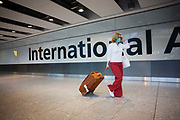 "Towing her suitcase after havng cleared International Customs, a masked female passenger walks through arrivals in Terminal 5 of Heathrow Airport. In the belief that she is protecting herself from airborne diseases and infections, the lady walks smartly through the concourse not wishing to be exposed to Swine Flu or perhaps SARS, in a hectic public place where such bacteria can be transmitted from one human being to another. From writer Alain de Botton's book project ""A Week at the Airport: A Heathrow Diary"" (2009)."