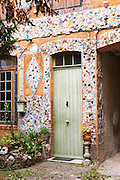 A hous and a door in Ampuis (Cote Rotie) decorated with pieces shards of porcelaine, one of the distinctive and unusual buildings in Ampuis across the street from Guigal's office.  Ampuis, Cote Rotie, Rhone, France, Europe