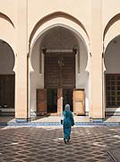 A woman walks through the courtyard at the Dar Batha Museum in Fes, Morocco
