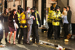 """© Licensed to London News Pictures . 15/12/2012 . Manchester , UK . Police rush to intervene in a fight . Revellers enjoy a wet but busy night out on one of the last weekends before Christmas , a traditionally busy time when office parties and clubbers decent on bars and clubs , often known as """" Mad Friday """" . Photo credit : Joel Goodman/LNP"""