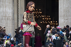 London, UK. 23rd October, 2021. Little Amal, a giant puppet of a Syrian refugee girl fleeing conflict, presents a wood carving of a ship at sea from St Paul's birthplace at Tarsus in Turkey to Dr David Ison, the dean of St Paul's Cathedral. The 3.5-metre puppet is nearing the end of an 8,000 km journey from the Turkish-Syrian border to Manchester in support of refugees.
