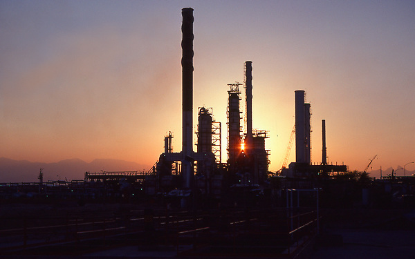 Stock photo of the sun setting behind a silhouetted chemical plant