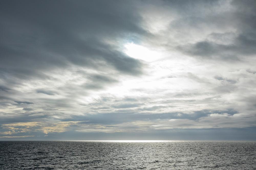 Sunlight breaking through the heavy cloud cover over the Strait of Juan de Fuca, as seen from San Juan Island, Washington, USA.