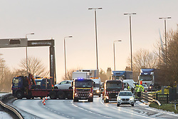 """© Licensed to London News Pictures. 01/12/2017. Bramham, UK. Picture shows the scene of a multiple vehicle incident on the north bound carriageway of the A1M near Bramham in Yorkshire that has left a lorry hanging over the edge of a bridge. A number of collisions have already been reported as snowfall through the night, coupled with freezing temperatures affected the region's roads. At around 7am, Highways England reported that two lanes were blocked on the A1 northbound within junction 44 due to a collision between multiple vehicles. A spokesperson for the agency said: """"Emergency services at scene, please take care on approach, delays are building. Photo credit: Andrew McCaren/LNP"""