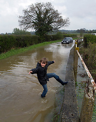 © London News Pictures. 29/04/2012. Margaretting, UK. A boy playing in flood water on a road near the town of Margaretting in Essex on April 29, 2012 . The nearby river Wid broke it's banks following torrential rainfall. Photo credit : Ben Cawthra /LNP
