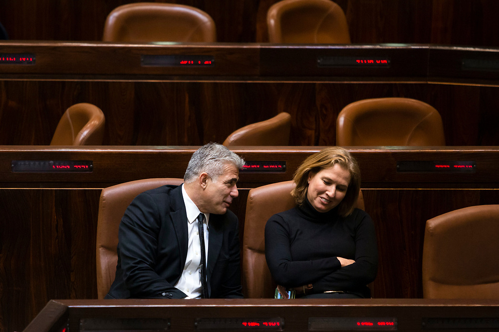 Israeli Minister of Finance Yair Lapid (L) and Israeli Minister of Justice Tzipi Livni (R) who were both fired by Prime Minister Benjamin Netanyahu the previous day chat at the Knesset, Israel's parliament, in Jerusalem, on December 3, 2014, during the vote to dissolve the parliament. Israeli legislators voted Wednesday to dissolve the parliament, and they set March 17 as the date for parliamentary elections, two years ahead of schedule, following a crisis within Prime Minister Netanyahu's coalition government.