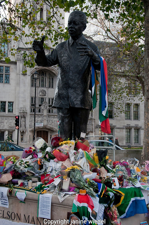 As a tribute to the death of Nelson Mandela mourners  brought flowers & messages and lit candles beneath his statue in Parliament Square London