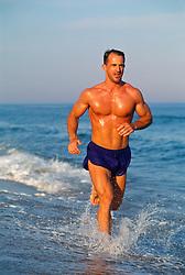 Good looking man jogging in the ocean