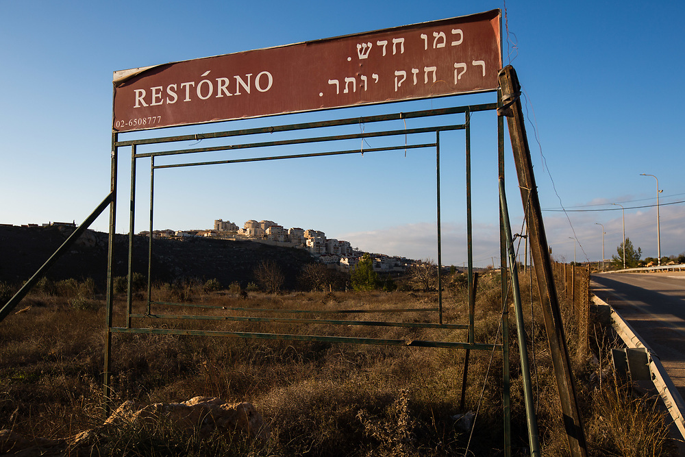 Houses at the West Bank Jewish settlement of Efrat in the Gush Etzion settlement bloc, are seen through a partially empty billboard, reading in Hebrew 'Like new, only stronger' near Givat HaDagan neighborhood, the northernmost neighborhood of Efrat which is situated on the southern outskirts of the Palestinian West Bank city of Bethlehem, on December 30, 2016.