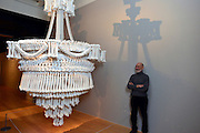"""© Licensed to London News Pictures. 14/11/2012. London, UK  Collector Richard Harris stands with """"In the Eyes of Others"""" a huge chandelier made of 3000 plaster cast bones by British artist Jodie Carey. Press preview of """"Death: A Self -Portrait. The Richard harris Collection"""" at The Welcome Collection today 14th November 2012. The exhibition showcases 300 works from a unique collection devote to the iconography of death and mankind's attitude towards it. Photo credit : Stephen Simpson/LNP"""