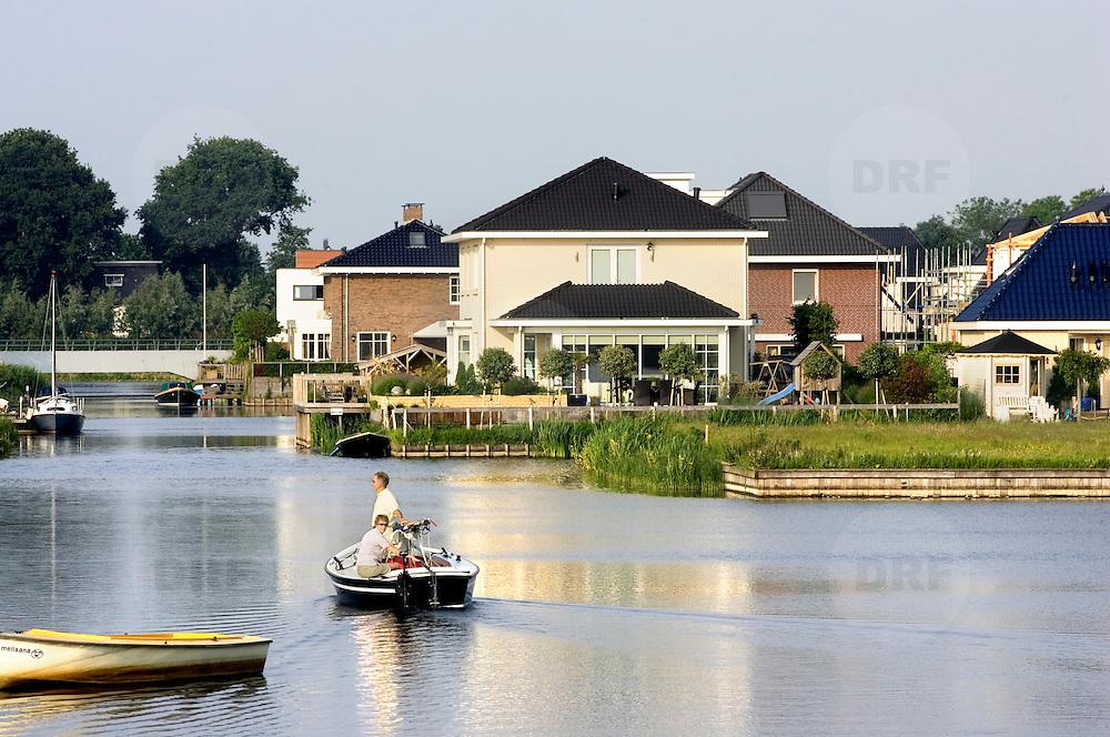 Nederland Zevenhuizen 25 mei 2007 20070525.Man en vrouw varen met sloep in watergang in nieuwbouwwijk..Serie tbv Schieland en de Krimpenerwaard, deze zorgt als waterschap voor droge voeten en schoon water in een bepaald gebied. Het beheersgebied van Schieland en de Krimpenerwaard strekt zich uit tussen Rotterdam, Schoonhoven en Zoetermeer. Binnen dit gebied zorgt Schieland en de Krimpenerwaard voor de kwaliteit van het oppervlaktewater, het waterpeil en de waterkeringen. Daarnaast beheert Schieland en de Krimpenerwaard een aantal wegen in de Krimpenerwaard...Foto David Rozing