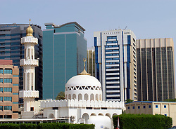 Contrast between mosque and modern office buildings in Abu Dhabi UAE