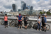 Five friends from different hoursolds maintan social distancing while standing opposite the skyline of the City of London, the capital's financial district, during the UK's Conoriavirus pandemic lockdown, on 7th June 2020, in London, England.