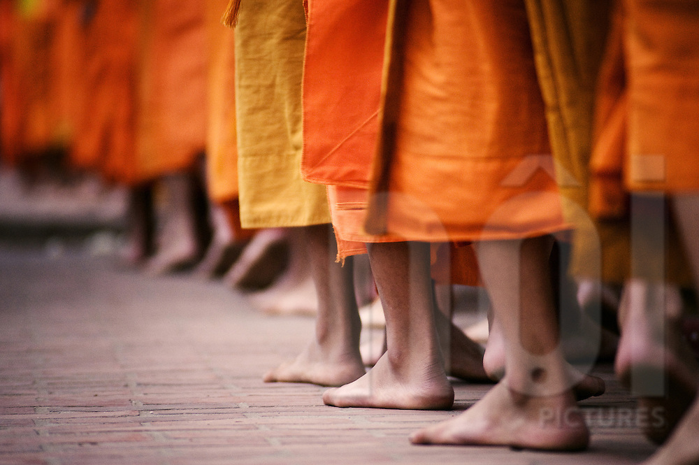 Silent procession of monks except the soft patter of their bare feet through Luang Prabang during alms, Laos, Southeast Asia