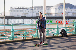 © Licensed to London News Pictures. 14/12/2016. Brighton, UK. A woman can be seen skateboarding on Brighton promenade as members of the public take advantage of the sunny and mild weather on the South Coast. Photo credit: Hugo Michiels/LNP