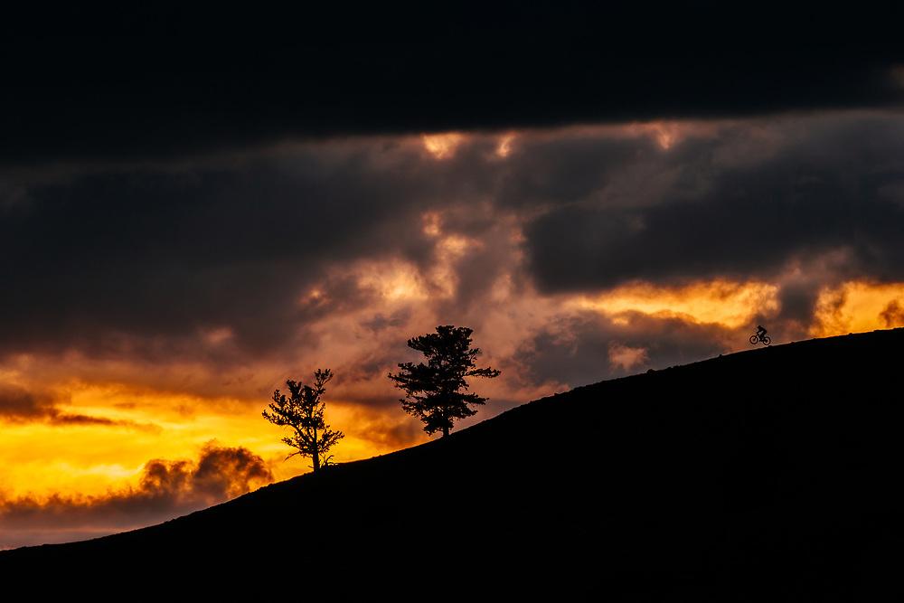 Malachi Artise rides a ridge as the clouds glow orange in the Tetons.
