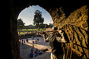 """5th February 2015, New Delhi, India. A man adjusts his scarf in an arched doorway in the ruins of Feroz Shah Kotla on the 5th February 2015<br /> <br /> PHOTOGRAPH BY AND COPYRIGHT OF SIMON DE TREY-WHITE a photographer in delhi. + 91 98103 99809. Email:simon@simondetreywhite.com<br /> <br /> People have been coming to Firoz Shah Kotla to leave written notes and offerings for Djinns in the hopes of getting wishes granted since the late 1970's. Jinn, jann or djinn are supernatural creatures in Islamic mythology as well as pre-Islamic Arabian mythology. They are mentioned frequently in the Quran  and other Islamic texts and inhabit an unseen world called Djinnestan. In Islamic theology jinn are said to be creatures with free will, made from smokeless fire by Allah as humans were made of clay, among other things. According to the Quran, jinn have free will, and Iblīs abused this freedom in front of Allah by refusing to bow to Adam when Allah ordered angels and jinn to do so. For disobeying Allah, Iblīs was expelled from Paradise and called """"Shayṭān"""" (Satan).They are usually invisible to humans, but humans do appear clearly to jinn, as they can possess them. Like humans, jinn will also be judged on the Day of Judgment and will be sent to Paradise or Hell according to their deeds. Feroz Shah Tughlaq (r. 1351–88), the Sultan of Delhi, established the fortified city of Ferozabad in 1354, as the new capital of the Delhi Sultanate, and included in it the site of the present Feroz Shah Kotla. Kotla literally means fortress or citadel."""