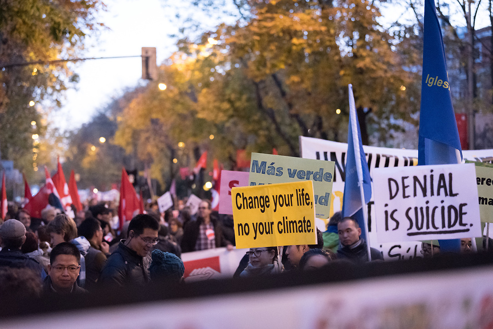 6 December 2019, Madrid, Spain: 'Change your life, no (sic) your climate' reads a sign, as thousands upon thousands of people march through the streets of central Madrid as part of a public contribution to the United Nations climate meeting COP25, urging decision-makers to take action for climate justice.