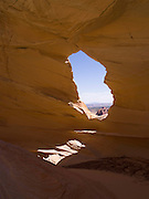 """Sandstone Window near Melody Arch, in the vicinity of North Coyote Buttes area known as """"The Wave,"""" Vermillion Cliffs National Monument, Arizona, known for its beautiful rock formations. Navajo Mountain is in the distance."""