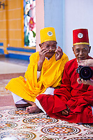 Cao Dai priests in red and yellow to represent the different branches of their religion.