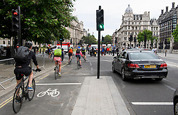 © London News Pictures. 25/08/2016. Cyclists pass through a red light while using a cycle lane on Abingdon Street, leading to Parliament Square. Cyclists repeatedly ignore new cycle lanes installed around westminster in central London. Between the hours of 8am and 9am on Wednesday 24/08/2016, 266 (two hundred and sixty six) cyclists passed through the red light at one of the newly installed  bike lanes and only 15 (fifteen) cyclists stopped.  The light system is designed to allow either vehicles or cyclists to pass at one time in order to make the junction safer for cyclists..... **VIDEO AVAILABLE** Photo credit: London News Pictures.