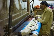 Indian man working loom at silk factory making textiles and saris at Bressler near Varanasi, Benares, Northern India