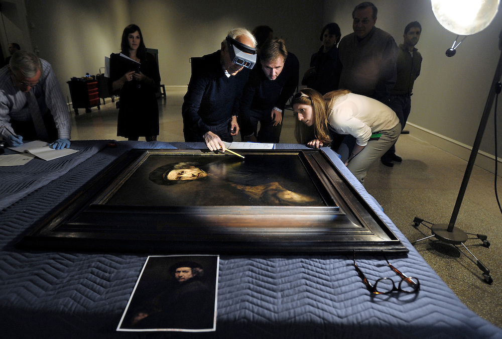Stephen Kornhauser, Chief Conservator at the Wadsworth Antheneum,  points out a scuff mark on he found on Rembrandt's Self Portrait from 1659 to Ulrich Birkmaier, Associate Paintings Conservator, center, and Nicole Stribling, Courier from The National Gallery of Art, where the painting is on loan from during a inspection and condition report before installation at the Wadsworth Atheneum Museum of Art in Hartford, Conn. (AP Photo/Jessica Hill)