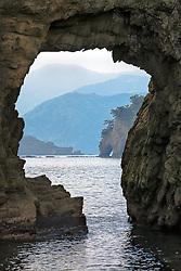 Futo Beach sea stack arch nicely frames the rugged landscape of the Dogashima coast on the Izu Peninsula of Japan