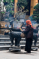 Old woman wearing a scarf plants incense in the burner as an offering whilst praying at quan su temple, Hanoi, Vietnam.