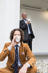 Two businessmen drinking coffee taking break