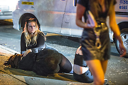 © Licensed to London News Pictures . 01/11/2015 . Manchester , UK . A woman comforts another who lies in the gutter on Deansgate Locks . Halloween revellers , wearing make up and costumes , out and about in Manchester City Centre . Photo credit : Joel Goodman/LNP