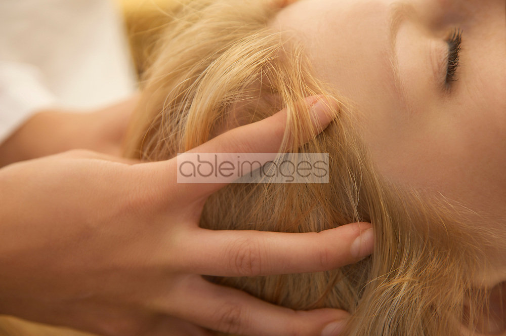 Extreme close up of woman head receiving scalp massage