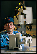 Industrial-robot designer Norio Kodaira of Mitsubishi smiles proudly behind his Melfa EN, a robot arm that moves with incredible speed and dexterity to assemble pieces, drill holes, make chips, or just about any repetitive task that needs to be done quickly and precisely. Like many Japanese roboticists, Kodaira was inspired as a child by Tetsuwan Atomu (Astro Boy), a popular Japanese cartoon about a futuristic robot boy who helps human beings (a 15-centimeter Astro Boy action figure). Astro Boy, drawn in the 1950's, will soon be the star of a major motion picture. In the story line, his birthdate is in April of 2003. Japan. From the book Robo sapiens: Evolution of a New Species, page 196.