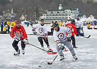 Matt Denton of the Ice Sages' team takes control of the puck with the T's Pub team during tournament action in the 50 plus division during the New England Pond Hockey Classic on Meredith Bay.    (Karen Bobotas/for the Laconia Daily Sun)