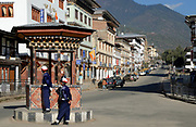 Two traffic policemen stand on traffic island in the centre of Thimpu.  Thimpu, Druk Yul, Bhutan. 13 November 2007.