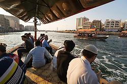 Passengers crossing The Creek by Abra water taxi in Deira, Dubai, United Arab Emirates