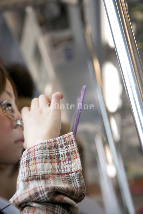young girl doing her makeup while riding the train