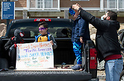HYANNIS - Thiago DeOlivera helps adjust his 5-year-old son, Michael's, mask while his other son Samuel, 8, and nephew, Nicholas, 8, hold a sign for hospital workers in the Cape Cod Hospital parking lot on Friday, April 10, 2020.